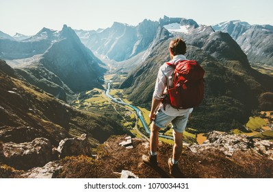 Hiking alone in Norway mountains Man with red backpack enjoying landscape on cliff solo traveling healthy lifestyle concept active summer vacations