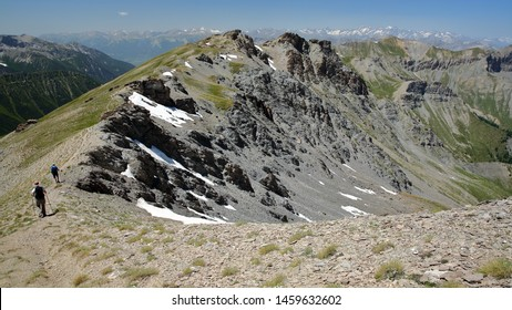 Hiking along a mountain ridge overlooking the two valleys of Saint Veran and Ceillac (Cristillan), with a montain range covered with snow in the background, Queyras Regional Natural Park, France