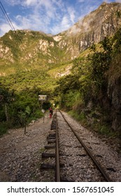 Hiking along the train tracks of Peru Rail on the road to Aguas calientes and Machupicchu. Cusco, Peru.