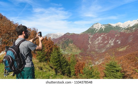 Hiking in Alps mountains. Man Traveler with Backpack hiking in the Mountains and making photo with his smartphone. mountaineering sport lifestyle concept