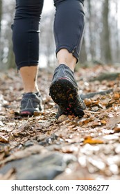 Hiking in autumn forest, sport shoes closeup