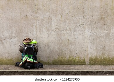 Hiking backpack with green towel, frying pan, sleeping bag, leather hat and green running shoes standing on a roadside in front of a gray wall
