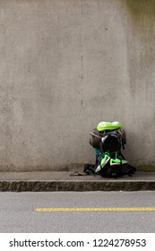 Hiking backpack with green towel, frying pan, sleeping bag and green running shoes standing on a roadside in front of a gray wall