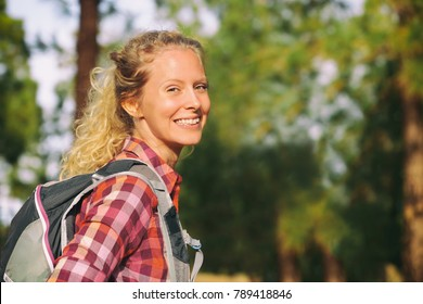 Hiking blonde woman healthy and active walking with backpack smiling happy in forest. Female hiker backpacker trekking in summer outdoors. Beautiful young adult girl living a happy lifestyle.