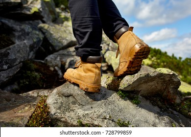 hiking boots close-up. girl tourist steps on the mountain trail on the rocks.
