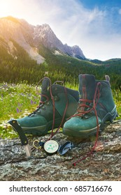 Hiking boots with knife on tree trunk with mountains in background