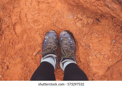 Hiking boots on red dirt.