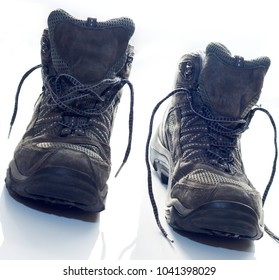 Hiking boots on white counter top after long day of walking. Laces undone. Walking boots at an angle.