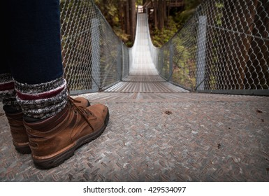 Hiking boots at the top of a suspension bridge in a forest.