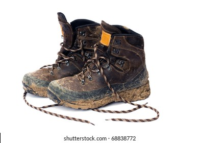 Hiking boots, well worn and muddy, isolated on white.