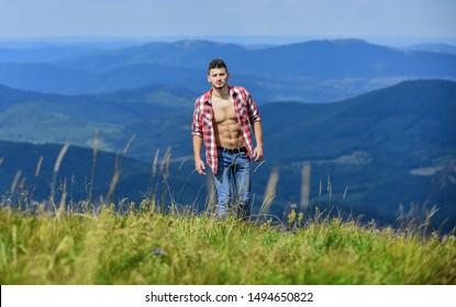 Hiking concept. Man stand top mountain landscape background. Muscular tourist walk mountain hill. Hiker muscular torso reach mountain peak. Athlete guy relax mountains. Beautiful environment.