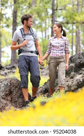 Hiking couple walking in forest. Young hikers couple enjoying romantic walk in spring forest with flower. Happy smiling interracial couple holding hands during hike in Tenerife, Canary Islands, Spain