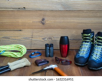 Hiking equipment like hiking boots, rope, ice axe, sunglasses, walking sticks with a wooden background. Preparation for adventures.