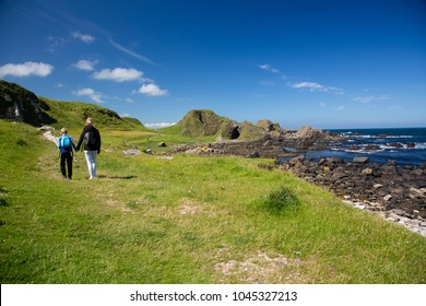 Hiking family, mother and child walks on green, grass covered field, North Ireland
