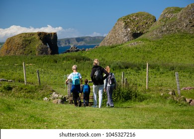 Hiking family, mother and three children walks on green, grass covered field, North Ireland
