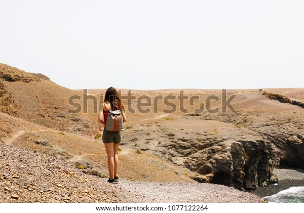 Hiking female walking on Lanzarote martian desertic landscape. Back view of young woman exploring volcanic island of Lanzarote, Canary Islands.