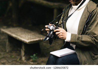The Hiking female or young woman watching photos from travel on digital camera.