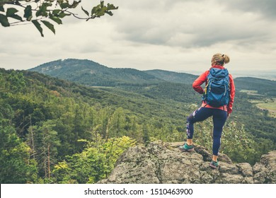 Hiking girl with backpack, looking at view. Travel and healthy lifestyle outdoors in fall season. Looking at mountains landscape.