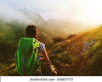 Hiking girl with backpack on the top of the mountain is looking at the sun