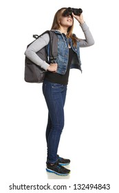 Hiking. Girl hiker with backpack looking through binoculars in full length
