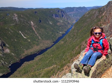 Hiking girl sitting at the top of Acropoles des Draveurs summit over the Hautes Gaurges de la Malbaie River and Canyon in Quebec, Canada