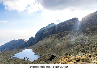 Hiking in High Tatras Mountains, Slovakia. Vysne Wahlenbergovo Pleso Lake (2154m) in Furkotska valley. Is the second highest situated lake in the Tatras. Sunset behind mount Ostra (2351m)