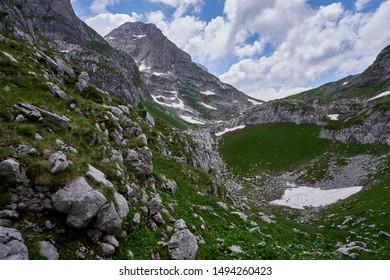 Hiking to the highest mountain of Montenegro - Zla Kolata. Trekking around rocks and snow of Prokletije National Park.