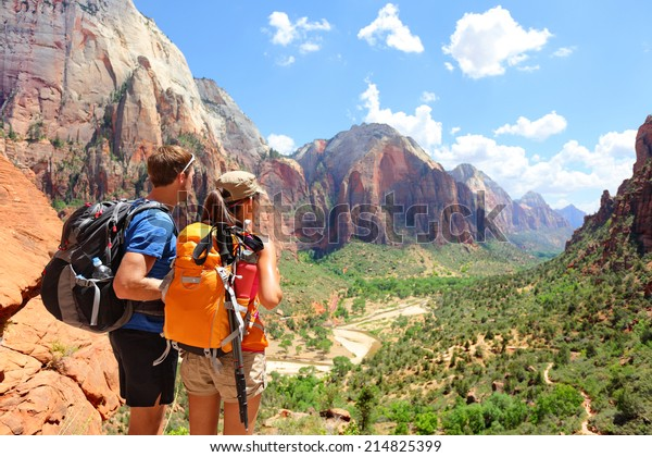 Hiking - hikers looking at view in Zion National park. People living healthy active lifestyle dong hike in beautiful nature landscape to Observation Point near Angles Landing, Zion Canyon, Utah, USA.