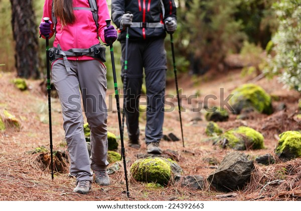 Hiking - Hikers walking in forest with poles on path in mountains. Close up of hiker shoes boots and hiking sticks poles. Man and woman hiking together.