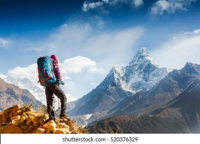 Hiking in Himalaya mountains. Woman Traveler with Backpack hiking in the Mountains. mountaineering sport lifestyle concept