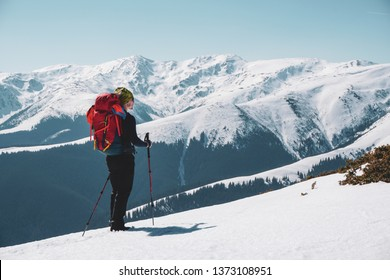 Hiking - male hiker with backpack admiring the view with snow-capped mountains in winter / early spring in Romania, Iezer-Papusa mountains