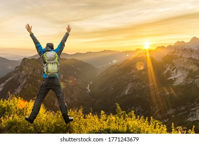 Hiking Man with Backpack jumping with raised arms on mountain. Amazing sunrise Backlight with beautiful lens flares and sunbeams. Julian Alps, Triglav National Park, Slovenia, Slemenova, Sleme.