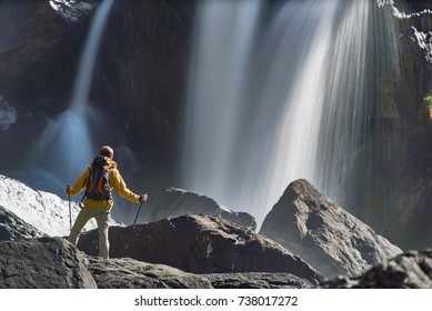Hiking man with backpack looking at waterfall in beautiful summer nature landscape. Portrait of male adult back standing outdoor.
