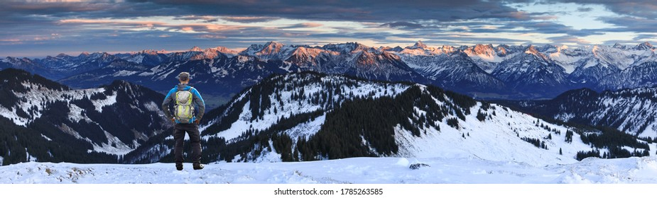 Hiking Man with Backpack standing in snow on winter mountain with view to amazing sunset alpenglow panorama of snow covered mountain ranges and dramatic clouds in cold winter. View from Riedbergerhorn