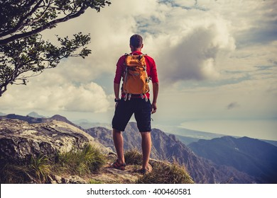 Hiking man, climber or trail runner in mountains, inspirational landscape. Motivated hiker with backpack looking at beautiful view. Trekking, travel and tourism concept. Fitness and healthy lifestyle.