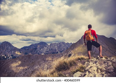 Hiking man, climber or trail runner in mountains, inspirational landscape. Motivated hiker with backpack looking at beautiful view. Travel, fitness and healthy lifestyle outdoors in summer nature.