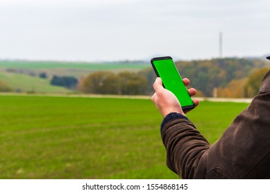 Hiking man with leather jacket using his smart phone to navigate in open autumn landscape. Using a cellphone to check map while doing outdoor activities in front of blurred landscape. Selective Focus