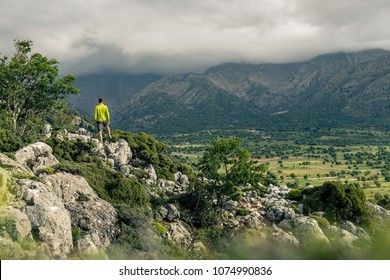 Hiking man looking at beautiful mountains inspirational landscape. Hiker trekking with backpack on rocky trail footpath. Healthy fitness lifestyle outdoors concept.