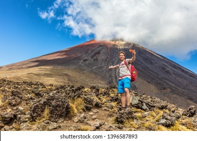 Hiking man on New Zealand Travel taking selfie at Tongariro Alpine Crossing hike trail. Happy hiker tramper phone photo of himself at volcanic mountains background. Summer adventure.