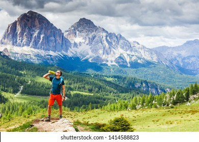 Hiking Man relaxing and drinking water after trekking with Dolomites mountains in the background, Italy.