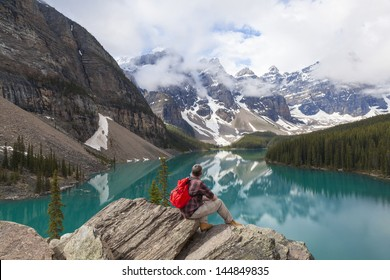 Hiking man sitting down with rucksack backpack on a rock by Moraine Lake looking at snow covered Rocky Mountain peaks, Banff National Park, Alberta Canada
