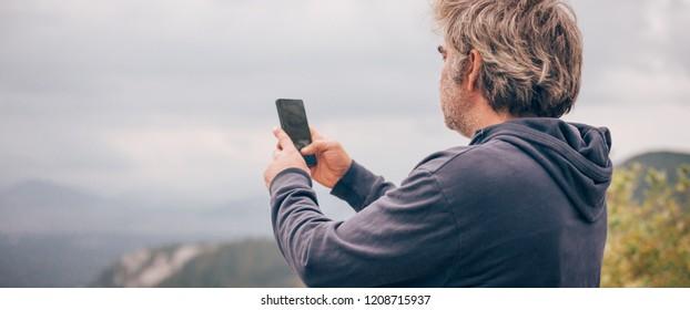 Hiking man taking panoramic picture of mountain landscape using smartphone. Zabljak Durmitor, Montenegro