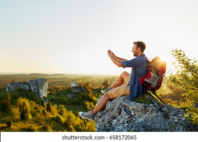 Hiking man taking photo with mobile phone sitting on top of the rock