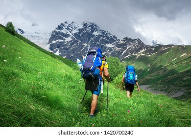 Hiking. Men on hiking trail. Trekking in mountains. Tourists with backpack hike to mountain peak. Sport tourism