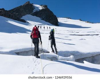 Hiking to mountain summit on snow glacier extreme trek