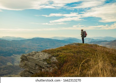 hiking mountain top edge of cliff highland scenic view with backpacker male person stay and looking side ways life style poster concept empty copy space for text