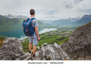 hiking in mountains, achievement concept, summer outdoors leisure activity, hiker with backpack enjoying the view of valley and lake