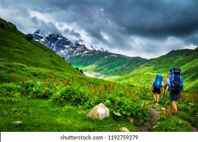 hiking in the mountains. Tourists with backpacks in mountain. Trekking in Svaneti region, Georgia. Two men hike in mount trail. Sport tourism in georgian grassy hills and rocky mountains with snow
