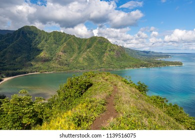 Hiking the narrow ridge on the dangerous Puu Manamana hike on Oahu, Hawaii.
