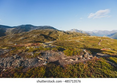 Hiking in Norway, classic norwegian scandinavian summer mountain landscape view with mountains, fjord, lake with a blue sky, near Geirangerfjord